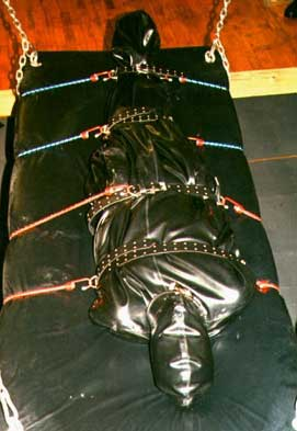 Sharina Nicole's latex fetishist Rubber kitty is strapped down in a latex bondage bag with bungee cords to the suspension swing at the Dungeon of Wrapture