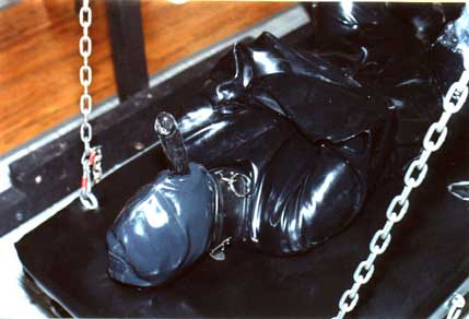 Dominatrix Sharina Nicole has strapped her submissive in a latex cat suit, latex straight jacket and fitted him with a fetish latex hood complete with rubber penis attachment.